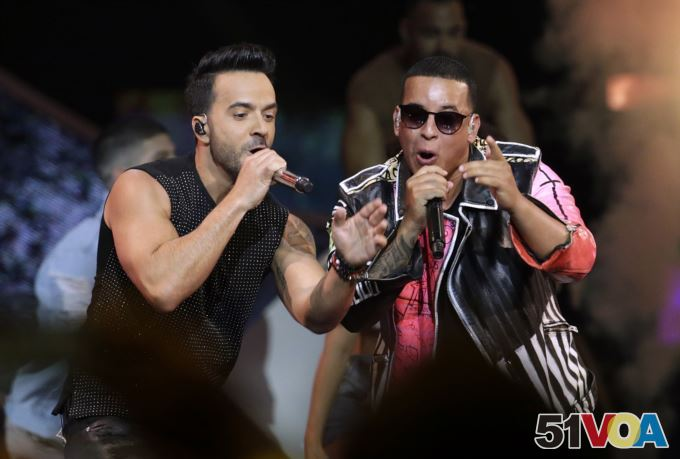 FILE - Singers Luis Fonsi, left and Daddy Yankee perform during the Latin Billboard Awards in Coral Gables, Florida.
