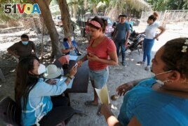An activist from the ruling Partido Nacional (National Party) holds the identification of a woman to register on a list to receive help from the government for the people affected by the floods caused by hurricanes Eta and Iota, in El Progreso, Honduras.