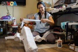 In this photo provided by Alaska Public Media, Carolina Tolladay Vadal is shown making a pinata in her home in Anchorage, Alaska, on April 14, 2021