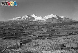 This 1947 photo shows the U.S. Army Williwaw camp on Alaska's Adak Island. Mount Moffett is in background. The Quonset huts are dug in as protection against the strong Aleutian winds. (AP Photo/Joseph D. Jamieson)