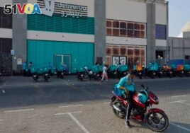 Delivery drivers for Deliveroo wait for orders, in Dubai, United Arab Emirates, Thursday, Sept. 9, 2021. Increasing online delivery orders has changed the city of Dubai. (AP Photo/Jon Gambrell)
