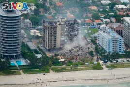 In this Friday, June 25, 2021, file photo, rescue personnel work in the rubble at the Champlain Towers South Condo, in Surfside, Fla. (AP Photo/Gerald Herbert, File)