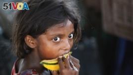 A child laborer eats a piece of a muskmelon near Jammu, India, June 12, 2015.
