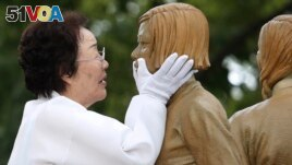 In this Aug. 14, 2019, file photo, Lee Yong-soo, who was forced to serve for the Japanese troops as a sex slave during World War II, touches the face of a statue of a girl symbolizing