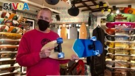 Co-owner of Uncle Funkys Boards, Jeff Gaites, holds a Surfskate, a skateboard, inside his shop in Manhattan, New York March 25, 2021.