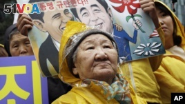 Former comfort woman Kil Un-ock who was forced to serve for the Japanese troops as a sexual slave during World War II, attends a rally against a visit by Japanese Prime Minster Shinzo Abe to the United States, in front of the Japanese Embassy in Seoul, South Korea, Wednesday, April 29, 2015. Abe has sidestepped a question on whether he would apologize for the sexual enslavement of women by Japan's army during World War II. The letters at a card read