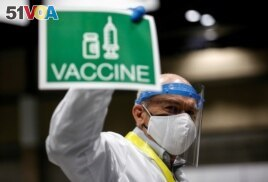 Doctor John Thayer holds up a sign to signal his station needs more vaccine doses in a coronavirus disease (COVID-19) vaccination site at Lumen Field Event Center in Seattle, Washington, March 13, 2021.