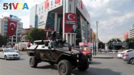 A special police vehicle drives in Kizilay Square with a poster of Turkey's President Recep Tayyip Erdogan in the background in Ankara, Turkey, Thursday, July 21, 2016. Turkey's Parliament approved a crackdown following an attempted coup last week. (AP Photo/Burhan Ozbilici)