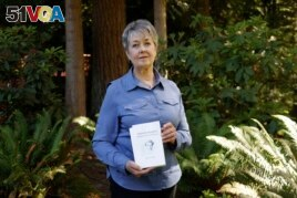 Karen McKnight stands in her backyard on Saturday, June 19, 2021, in Sammamish, Wash., holding two books written by her brother Ross Bagne of Cheyenne, Wyo. (AP Photo/John Froschauer)
