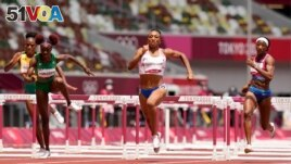Jasmine Camacho-Quinn, of Puerto Rico, center, races to the line to win the gold in the women's 100-meters hurdles final at the 2020 Summer Olympics, Monday, A