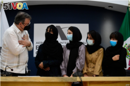 The Mexican Secretary of Foreign Affairs Marcelo Ebrard (L) welcomes four Afghan women, members of the Afghanistan Robotic team, during their arrival to Mexico after asking for refuge, at the Airport in Mexico City, on August 24, 2021.