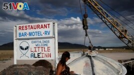 In this July 22, 2019 photo, Grace Capati looks at a UFO display outside of the Little A'Le'Inn, in Rachel, Nevada, the closest town to Area 51.