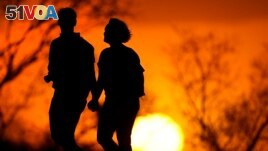 In this Wednesday, March 10, 2021 file photo, a couple walks through a park at sunset in Kansas City, Missouri, USA. According to a new report, U.S. life expectancy fell by a year and a half in 2020, the largest one-year decline since World War II. (AP Photo/Charlie Riedel)