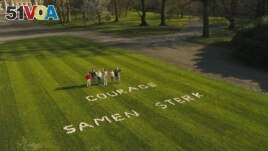 In this image from VTM video, Belgium's King Philippe, right, stands with members of his family in the Royal Gardens of Laeken with a message 'Courage, strong together' written on the lawn on April 4, 2020. (VTM via AP)