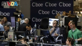 Traders work in a trading pit at the Chicago Board Options Exchange, Monday, Dec. 11, 2017, in Chicago, as they trade futures and options unrelated to bitcoin. Trading in bitcoin futures began Sunday on the CBOE. (AP Photo/Kiichiro Sato)