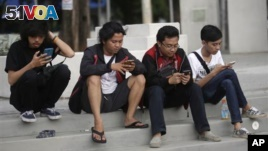People look at their smartphones as they play