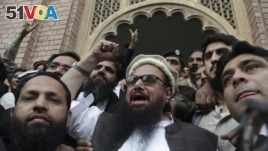 Hafiz Saeed, head of the Pakistani religious party, Jamaat-ud-Dawa, gestures outside a court in Lahore, Pakistan, Nov. 22, 2017.