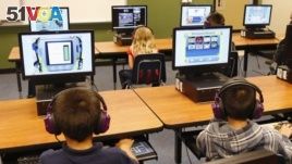 In this July 21, 2014 file photo, students at a summer reading academy at Buchanan elementary school work in the computer lab at the school in Oklahoma City.