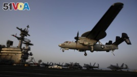 In this Aug. 10, 2014, photo, an aircraft lands after missions targeting the Islamic State group in Iraq from the deck of the U.S. Navy aircraft carrier USS George H.W. Bush in the Persian Gulf.