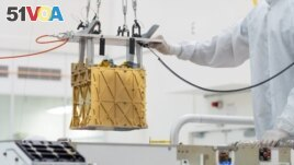 Technicians at NASA's Jet Propulsion Laboratory lower the Mars Oxygen In-Situ Resource Utilization Experiment (MOXIE) instrument into the belly of the Perseverance rover in an undated photograph in Pasadena, California, U.S. (NASA/JPL-Caltech/Handout via REUTERS )