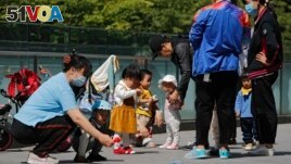 Residents bring their children to play in a compound near a commercial office building in Beijing on May 10, 2021. (AP Photo/Andy Wong)