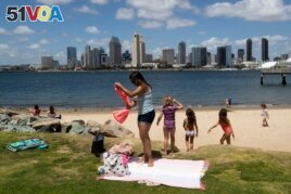 FILE - In this May 19, 2020, file photo, a family sets up at a beach looking out toward the San Diego skyline in Coronado, Calif.