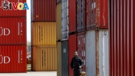An Argentina tax official and his sniffer dog are shown by containers loaded with grains at the port in Argentina. (File)