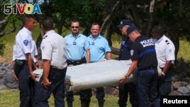 French gendarmes and police carry a large piece of plane debris which was found on the beach in Saint-Andre, on the French Indian Ocean island of La Reunion, July 29, 2015. (REUTERS/Zinfos974/Prisca Bigot)