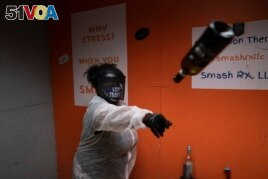 La Shaun Aaron, 43, throws a wine bottle into a wall during a session to help relieve stress at Smash Rx, Feb. 5, 2021. (AP Photo/Jae C. Hong)