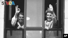 In this 1985 file photo, President Ronald Reagan gives the A OK sign from the window of his hospital room at the Naval Medical Center in Bethesda, Maryland as first lady Nancy Reagan waves to a small group below. The president is recovering from surgery performed Saturday to remove a cancerous polyp. (AP Photo/Scott Stewart)