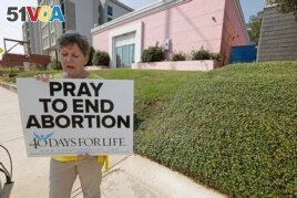 FILE - In this Oct. 2, 2019. file photo, an abortion opponent sings to herself outside the Jackson Womens Health Organization clinic in Jackson, Miss. (AP Photo/Rogelio V. Solis, File)