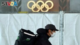 An Uber Eats delivery person carries items near the Japan National Stadium, where opening ceremony and other events are planned for postponed Tokyo 2020 Olympics, on Tuesday, April 6, 2021, in Tokyo. (AP Photo/Eugene Hoshiko)