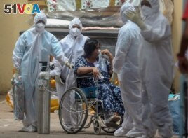 Health workers attend to a patient at the Jumbo COVID-19 hospital in Mumbai, India, Thursday, April 22, 2021. New infections are rising faster in India than any other place in the world.