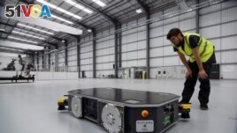 An engineer at UK electric van and bus maker Arrival inspects a specially developed autonomous robot at the startup's low-cost