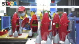 In this May 27, 2020, photo released by Xinhua News Agency, a worker makes plastic toys at a factory in Zhangjiajie, central China's Hunan Province.