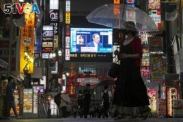 Pedestrians walk past a giant public TV with a live broadcast of a news conference by Japanese Prime Minister Yoshihide Suga after he announced a state of emergency because of rising coronavirus infections Thursday, July 8, 2021, in Tokyo.
