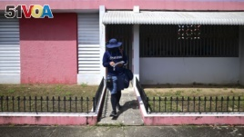 Postal worker Jose Montoya does his rounds in Carolina, Puerto Rico, Thursday, Oct. 1, 2020. More than half of all homes in Puerto Rico lack a physical address, so the absence of street names and numbers also have created multiple problems. (AP Photo/Carlos Giusti)