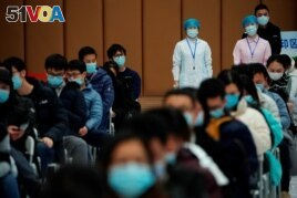 People sit at a vaccination site after receiving a dose of a coronavirus disease (COVID-19) vaccine, during a government-organised visit, following the coronavirus disease (COVID-19) outbreak, in Shanghai, China January 19, 2021.