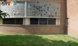 Broken windows are seen outside Cody High School in Detroit on Friday, Aug. 20, 2021. (AP Photo/Carlos Osorio)