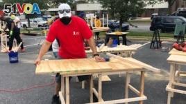 In this photo provided by Jessica Berrellez, her husband, Al Berrellez, builds a desk in Gaithersburg, Md., on Friday, Sept. 25, 2020. (Jessica Berrellez via AP)