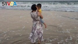 In this photo released by Zou Xiaoqi, Zou Xiaoqi, a single mother turned activist in Shanghai, holds her son as they visit a beach in Sanya, southern China's Hainan province in October, 2019.