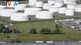In this Sept. 8, 2008 file photo, traffic on I-95 passes oil storage tanks owned by the Colonial Pipeline Company in Linden, N.J. (AP Photo/Mark Lennihan, File)