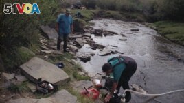 FILE - Elden Kinderknetch was looking for gold near Atlantic City, Wyoming on Sept. 13, 1998. The stepping stones made it easier to cross the creek. (AP File Photo)