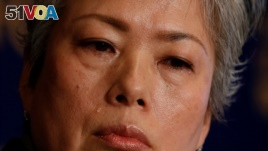 Noriko Matsumoto who fled with her children from Japan's Fukushima prefecture after the nuclear disaster, cries during a news conference in Tokyo, Jan. 17, 2017.