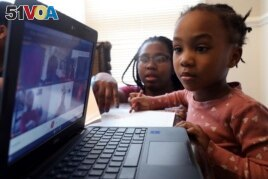 Lear Preston, 4, who attends Scott Joplin Elementary School, participates in her virtual classes as her mother, Brittany Preston, background, assists at their residence in Chicago's South Side, Wednesday, Feb. 10, 2021. (AP Photo/Shafkat Anowar)