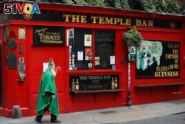 A man dressed as St. Patrick walks past a closed pub in Dublin, Ireland, March 16, 2020. (AP File Photo)