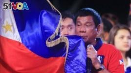 Philippine president Rodrigo 'Digong' Duterte holds a Philippine flag while addressing his supporters.
