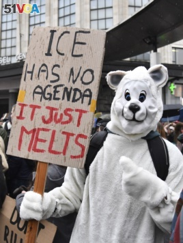 A protestor wearing a polar bear suit holds a placard during a demonstration against climate change in Brussels, Thursday, Jan. 17, 2019. (AP Photo/Geert Vanden Wijngaert)