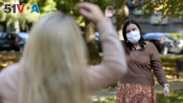 Women exercise during a therapy session in a park in Sarajevo, Bosnia Monday, Oct. 26, 2020. (AP Photo/Kemal Softic)