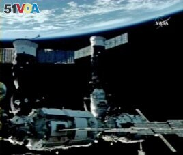In this image from NASA Television, Earth is the background as the International Space Station is seen during a space walk by Cosmonauts Fyodor Yurchikhin and Oleg Kotov